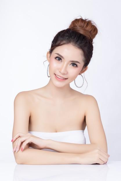 Portret van aantrekkelijke aziatische vrouwenzitting die op witte achtergrond glimlachen. Premium Foto