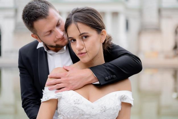 Portret van aantrekkelijke brunette bruid en knappe bruidegom Gratis Foto