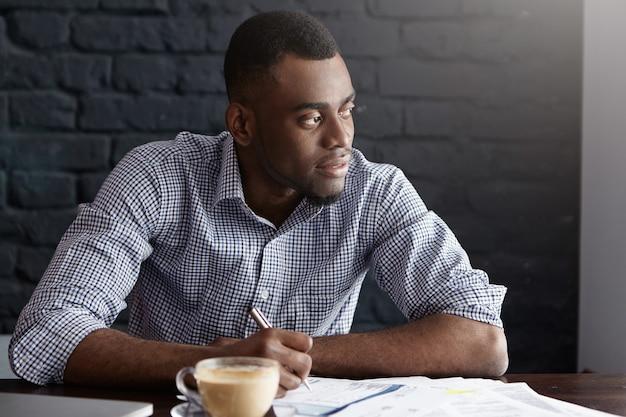Portret van aantrekkelijke jonge afrikaans-amerikaanse ceo die in overhemd wat administratie doorneemt Gratis Foto