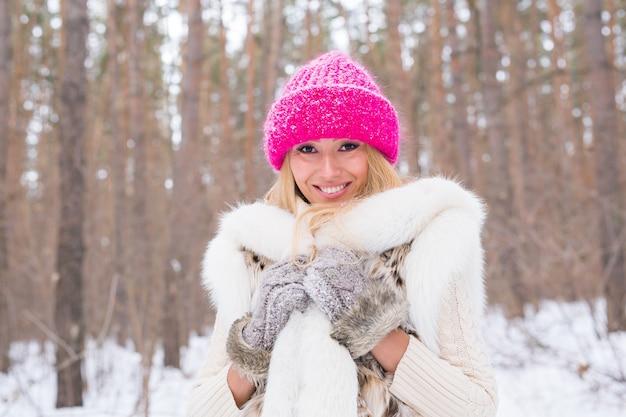 Portret van aantrekkelijke jonge blonde vrouw gekleed in witte jas en Premium Foto