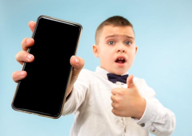 Portret van aantrekkelijke jonge jongen die lege smartphone houdt Gratis Foto