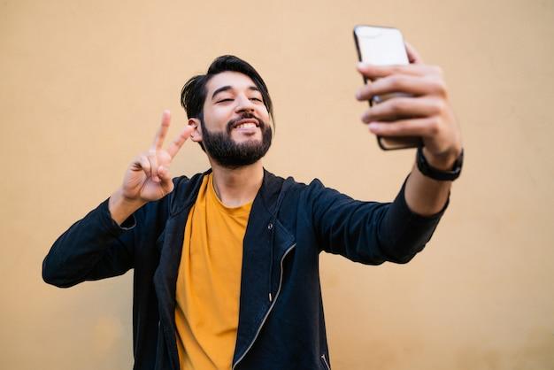 Portret van aantrekkelijke jonge man die selfies met zijn mophile telefoon neemt tegen gele muur. Gratis Foto