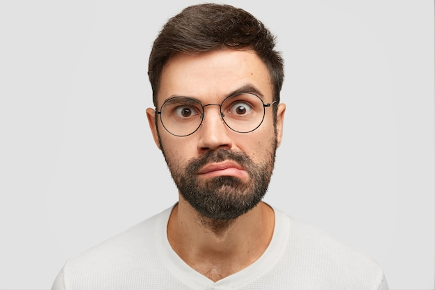 Portret van aantrekkelijke jonge man met donkere stoppels close-up, ziet er verrassend uit Gratis Foto