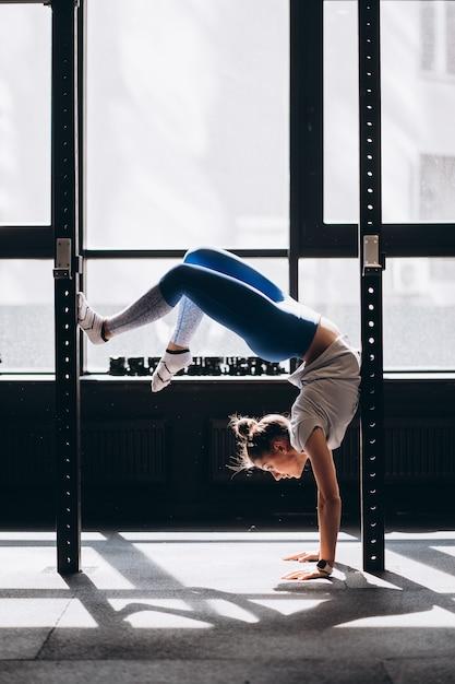 Portret van aantrekkelijke jonge vrouw die yoga of pilates oefening doet Gratis Foto