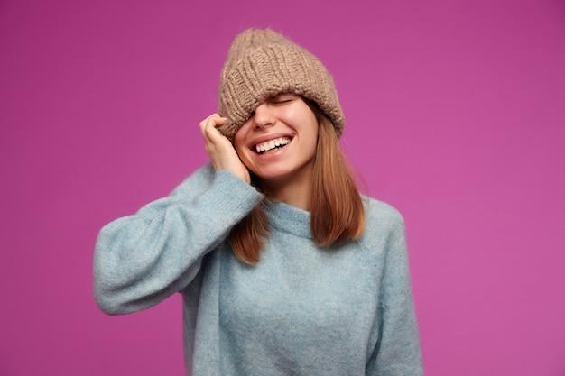 Portret van aantrekkelijke, jonge vrouw met donkerbruin lang haar. het dragen van blauwe trui en gebreide muts. trekt hoed over oog en lachend op geïsoleerde over paarse muur Gratis Foto