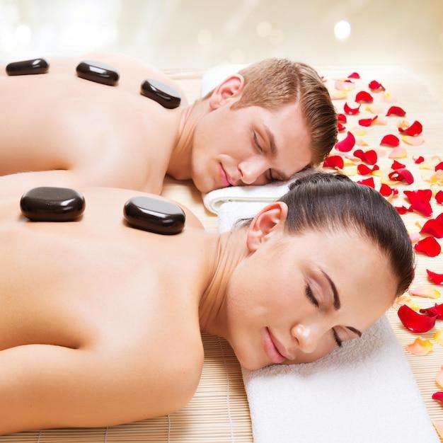 Portret van aantrekkelijke paar ontspannen in spa salon met hete stenen op lichaam. Gratis Foto