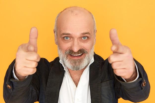Portret van aantrekkelijke positieve zakenman van middelbare leeftijd met kaal hoofd en grijze baard wijzende wijsvingers op camera en vol vertrouwen glimlachen. succes, carrière en vertrouwen. selectieve aandacht Gratis Foto