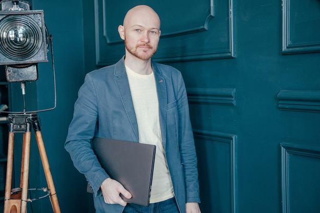 Portret van aantrekkelijke volwassen succesvolle kale bebaarde man in pak met laptop in de buurt van blauwe muur Premium Foto