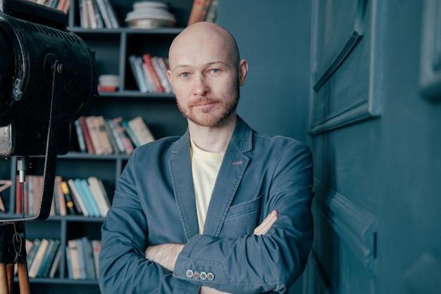 Portret van aantrekkelijke volwassen succesvolle kale man met baard in pak tegen boeken muur Premium Foto