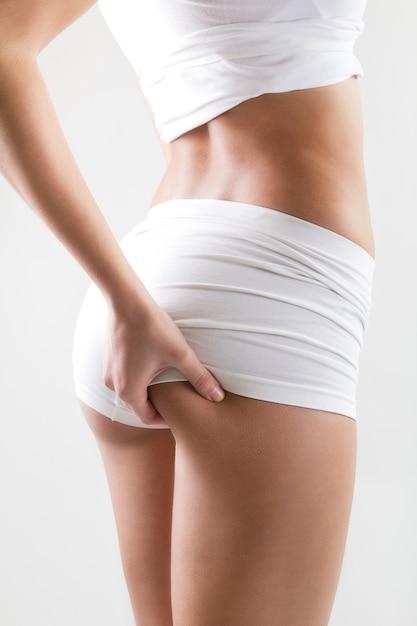 Portret van aantrekkelijke vrouw met perfect lichaam controleert cellulitis op haar billen Gratis Foto