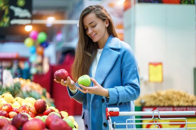Portret van aantrekkelijke vrouwenkoper met kar in de kruidenierswinkelwinkel tijdens het kiezen van en het kopen van verse appelen bij fruitafdeling Premium Foto