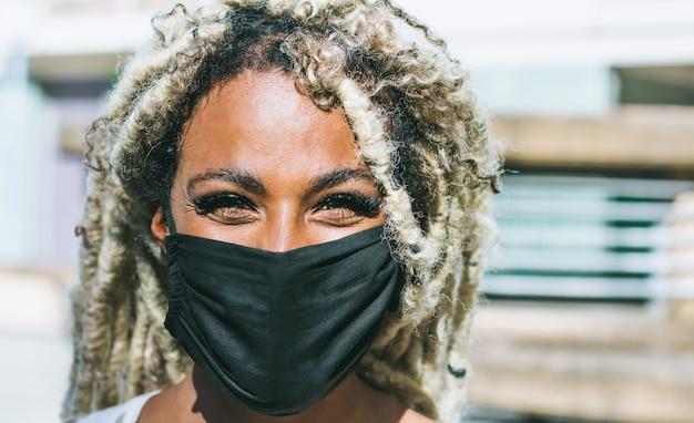 Portret van afrikaans meisje met blonde dreadlocks die gezichts beschermend masker dragen voor coronavirus-preventie Premium Foto