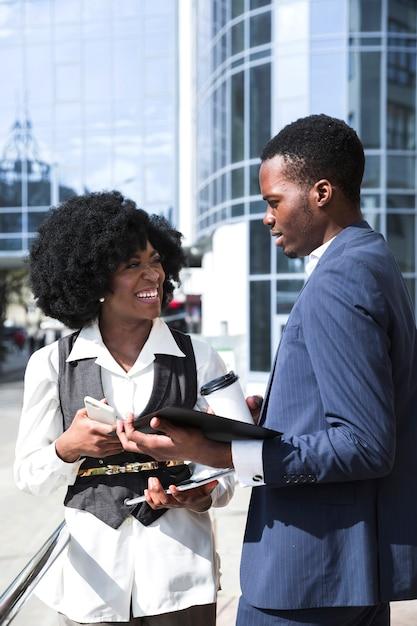 Portret van afrikaanse collega twee die voor de bouw staat die aan elkaar spreken Gratis Foto