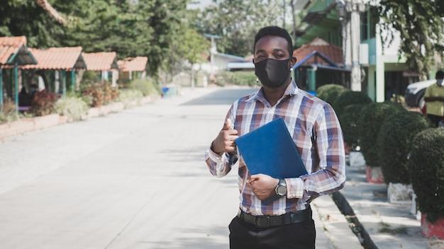 Portret van afrikaanse leraar in gezichtsmasker die zich buiten op school bevindt Premium Foto