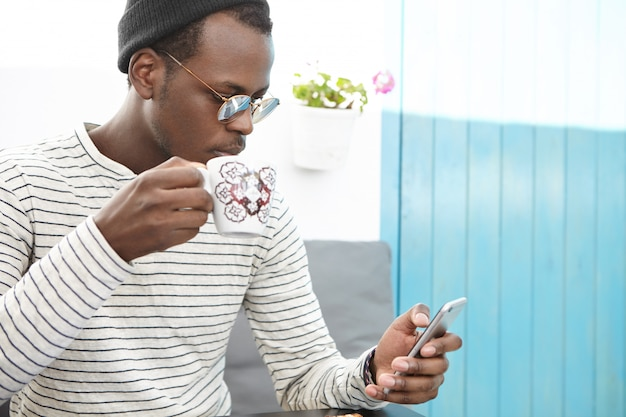 Portret van afrikaanse man in stijlvolle kleding met mok, het drinken van verse koffie, surfen op internet en het controleren van nieuwsfeed op sociale media, met behulp van mobiele telefoon tijdens het ontbijt in café met gezellige stoelen Gratis Foto
