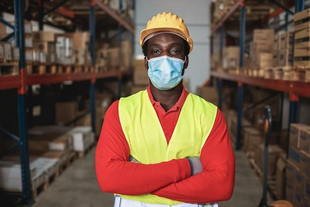 Portret van afrikaanse werknemer man in magazijn terwijl het dragen van veiligheidsmasker - focus op man ogen Premium Foto