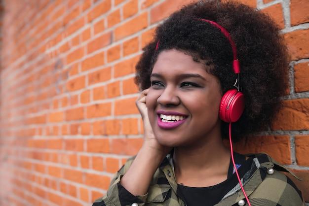 Portret van afro-amerikaanse latijns-vrouw glimlachend en luisteren naar muziek met koptelefoon tegen bakstenen muur. buitenshuis. Gratis Foto