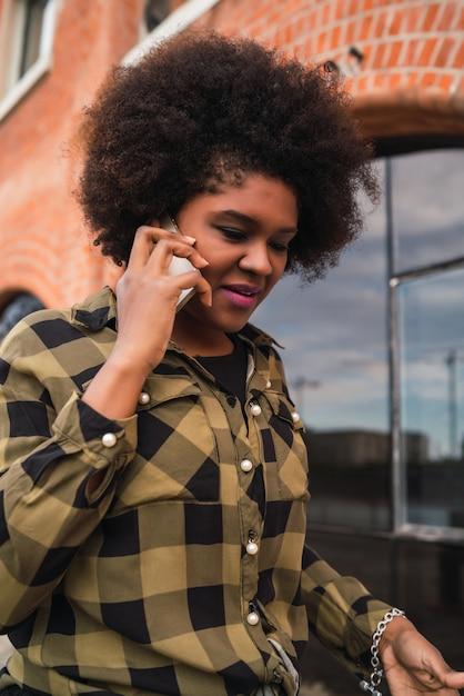 Portret van afro latijns-vrouw praten aan de telefoon buiten in de straat. stedelijk en communicatieconcept. Gratis Foto