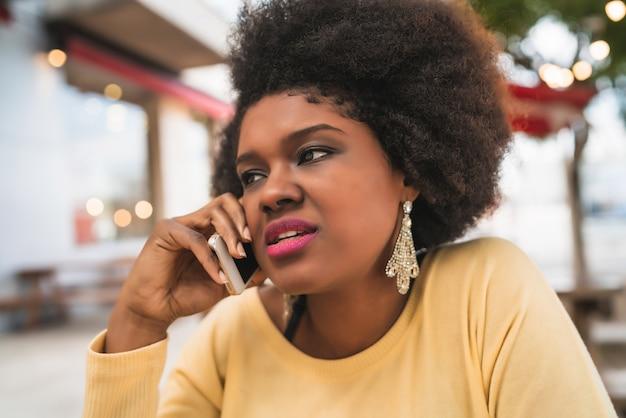 Portret van afro latijns-vrouw praten aan de telefoon zittend op coffeeshop. communicatie concept. Gratis Foto