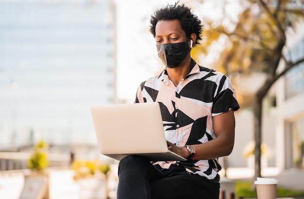Portret van afro toeristische man met behulp van zijn laptop en het dragen van een beschermend masker terwijl hij buiten zit Gratis Foto