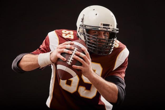 Portret van amerikaanse voetballer die een bal met beide handen houdt Premium Foto