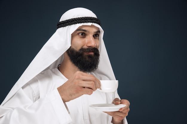Portret van arabische saoedische man. jong mannelijk model dat en koffie of thee bevindt zich drinkt. Gratis Foto