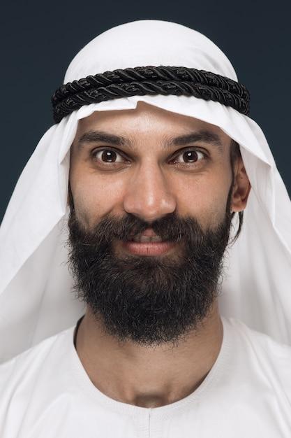 Portret van arabische saoedische sjeik close-up. jonge mannelijke model staan en glimlachen, ziet er gelukkig uit. Gratis Foto