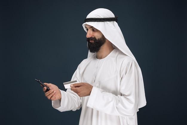 Portret van arabische saoedische sjeik. man met smartphone voor het betalen van rekening, online winkelen of wedden. Gratis Foto