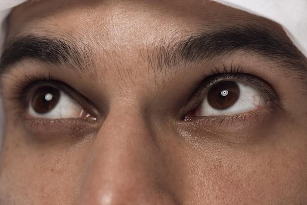 Portret van arabische saoedische zakenman close-up. het gezicht van het jonge mannelijke model, schot van ogen kijkt omhoog. concept van zaken, financiën, gezichtsuitdrukking, menselijke emoties. Gratis Foto