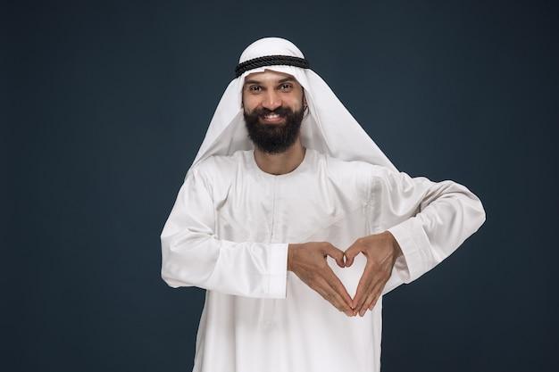 Portret van arabische saoedische zakenman. jong mannelijk model dat a toont een gebaar van een hart bevindt. concept van zaken, financiën, gezichtsuitdrukking, menselijke emoties. Gratis Foto
