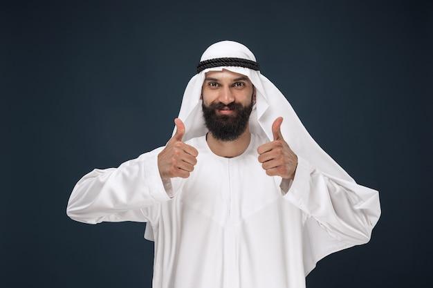 Portret van arabische saoedische zakenman. jong mannelijk model dat zich a toont een gebaar van een duim omhoog. concept van zaken, financiën, gezichtsuitdrukking, menselijke emoties. Gratis Foto