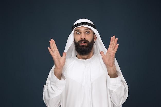 Portret van arabische saoedische zakenman op donkerblauwe studioachtergrond. jong mannelijk model dat geschokt en verbaasd staat. concept van zaken, financiën, gezichtsuitdrukking, menselijke emoties. Gratis Foto