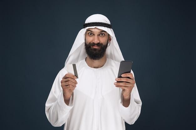 Portret van arabische saoedische zakenman op donkerblauwe studioachtergrond. man met smartphone voor het betalen van rekening, online winkelen of wedden. concept van zaken, financiën, gezichtsuitdrukking, menselijke emoties. Gratis Foto