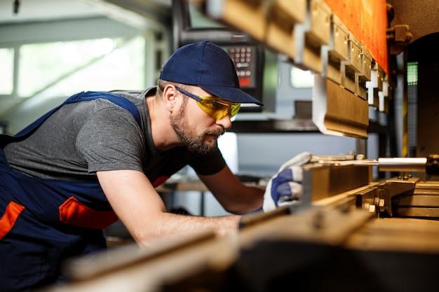 Portret van arbeider dichtbij metaalbewerkende machine Gratis Foto