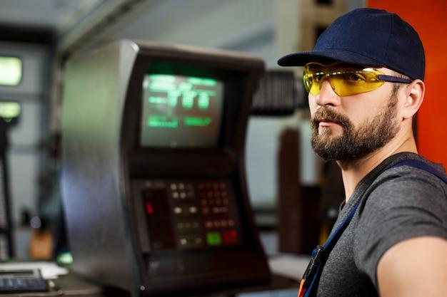Portret van arbeider in onalls dichtbij computer, de achtergrond van de staalfabriek. Gratis Foto