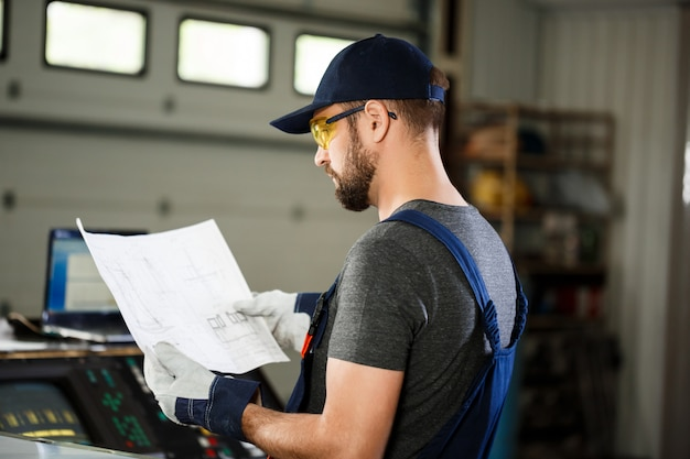 Portret van arbeider in overall, de achtergrond van de staalfabriek. Gratis Foto