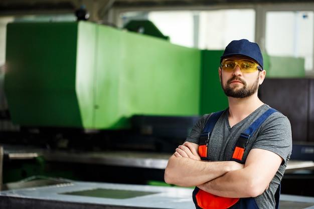 Portret van arbeider met gekruiste wapens, de achtergrond van de staalfabriek. Gratis Foto