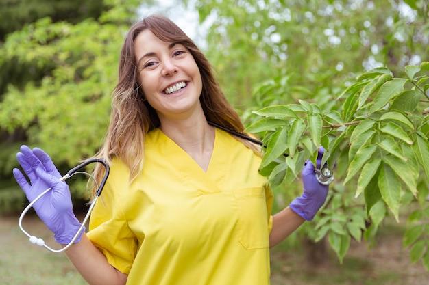 Portret van arts die gelukkig met haar handen een stethoscoop houdt Premium Foto