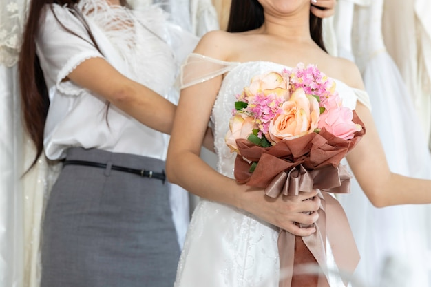 Portret van aziatisch homoseksueel paar in bruidkleding die kleding in een winkel kiezen. lgbt-lesbienne concept. Premium Foto