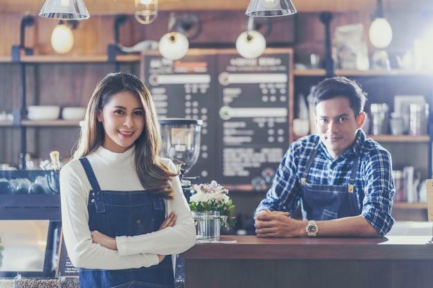 Portret van aziatische jonge kleine bedrijfseigenaar met koffiewinkel voor tegenbar, ondernemer en opstarten Premium Foto