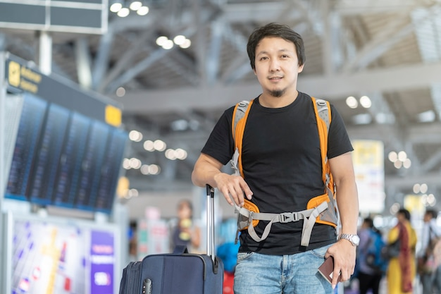 Portret van aziatische reiziger met bagage met paspoort die zich over de vluchtraad voor c bevinden Premium Foto