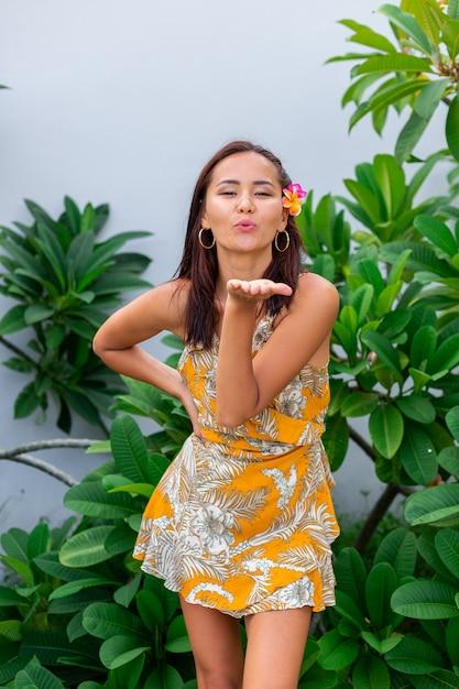 Portret van aziatische vrouw in gele zomerjurk staat met plumeria thaise bloem in haar en ronde oorbellen Gratis Foto