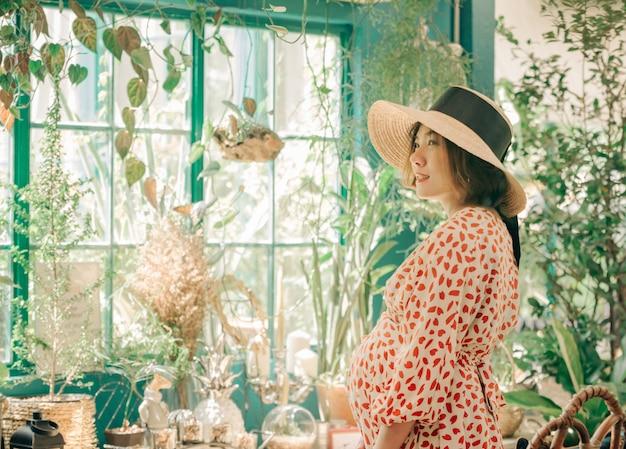 Portret van aziatische vrouw met hoed die in toon van de de koffie de uitstekende kleur van de de zomerkoffie glimlachen. Premium Foto