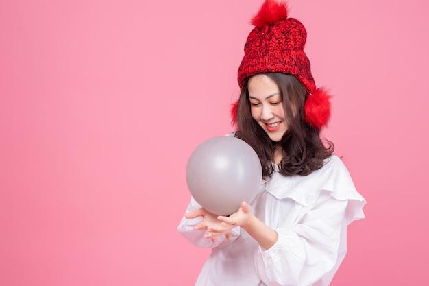 Portret van aziatische vrouw op wit overhemd en de rode ballon van de hoedenholding in de hand. gelukkig model lachend op roze Premium Foto