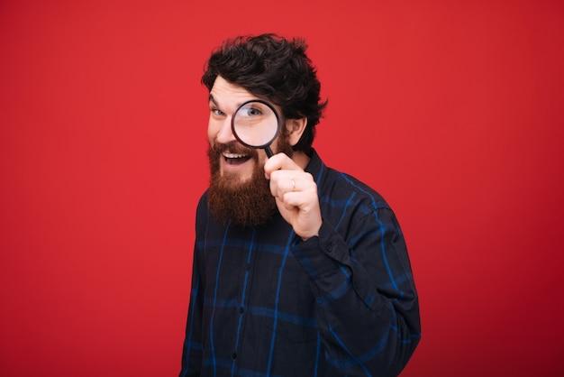 Portret van bebaarde man kijkt door een vergrootglas over rode muur Premium Foto