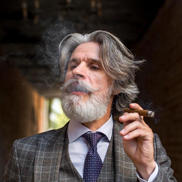 Portret van bebaarde volwassen man roken Gratis Foto