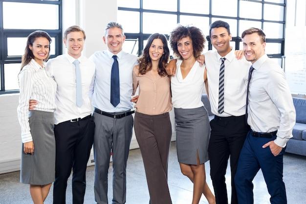 Portret van bedrijfsmensen die zich en in bureau glimlachen verenigen Premium Foto