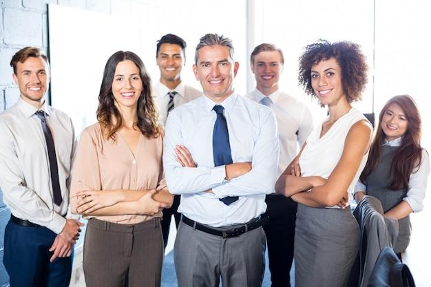 Portret van bedrijfsmensen die zich met die wapens bevinden in bureau worden gekruist Premium Foto