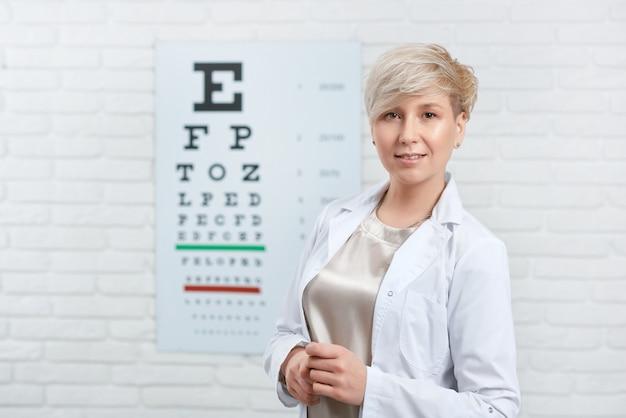 Portret van bekwame oftalmoloog die voor visuele inspectietafel blijven Premium Foto