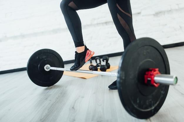 Portret van benen sportieve vrouw met barbell. isolatet op grijze vloer! levensstijl. Premium Foto